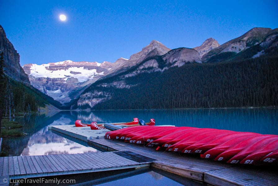 A full moon illuminates the Lake Louise boathouse
