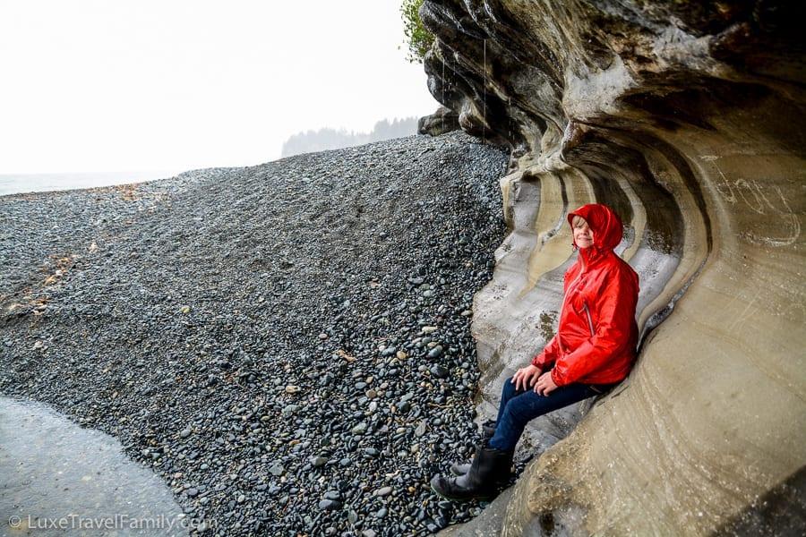 A boy sitting under a cliff near the waterfall at Sandcut Beach