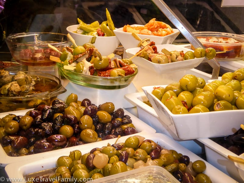 Bowls of olives, onions and peppers in the display case at at Conserves Gloria