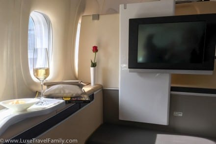 Single red rose, Escada amenity kit, Monocle magazine, glass of champagne next to the windows in Lufthansa first class cabin