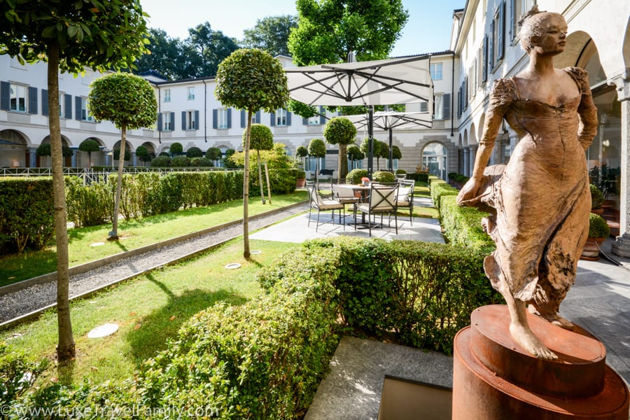 Statue of a woman, box hedge, topiaries and sitting areas in the courtyard at Four Seasons Milano