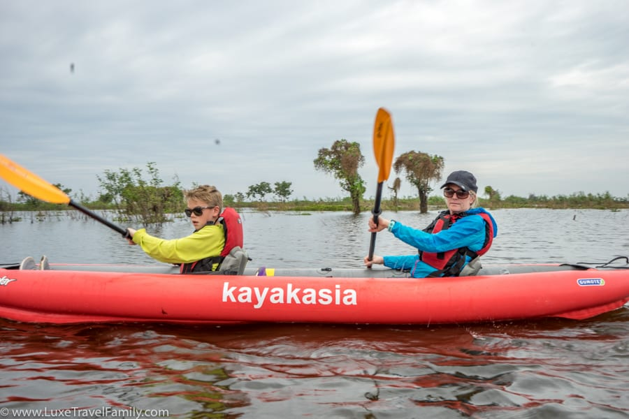 Family kayaking on Tonle Sap Lake with Smiling Albino
